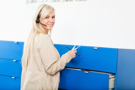 Portrait of a young woman in front of wall drawers with documents Stock Photo - 9282766