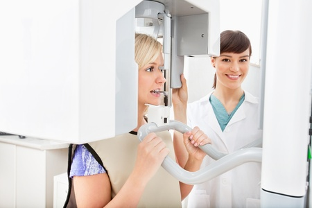 A young dentist taking a panoramic digital X-ray of a patient`s teeth photo