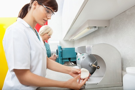 prosthetic equipment: Side view of female technicians using smoothing dental impressions