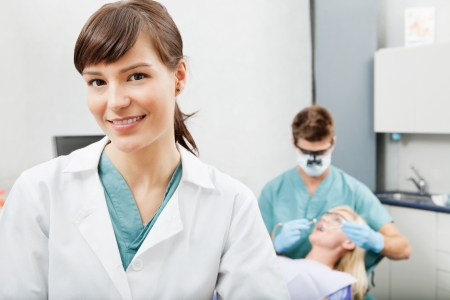 dental nurse: Portrait of a dental assistant smiling with dentistry work in the background