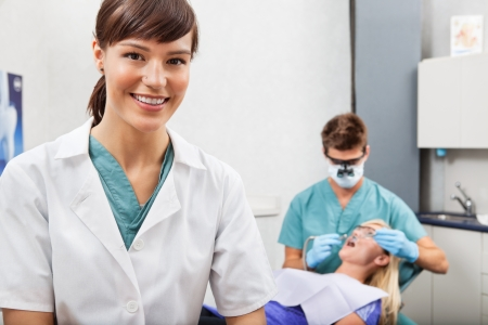 assistant: Portrait of dental assistant smiling with dentistry work in the background