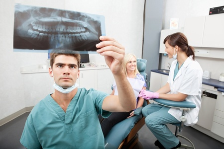 Radiodentist checking x-ray with assistant and patient having conversation in the background photo