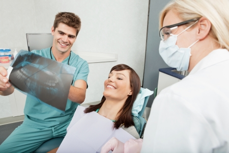 Smiling male dentist explaining the details of x-ray to a beautiful female patient photo