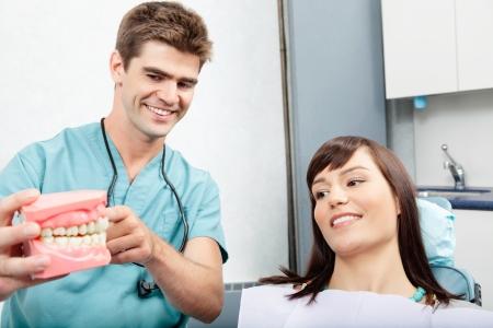 dentadura postiza: Dentista masculino explicando una dentadura paciente mujer trabajan en la cl�nica dental