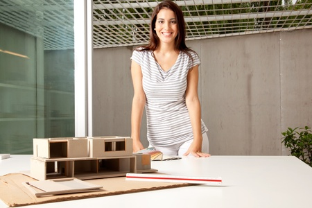architectural studies: A young architect in an office with a rough model of a house Stock Photo