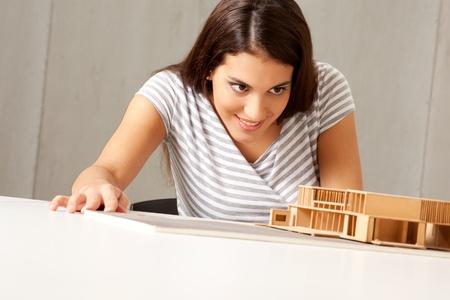 female architect: A female architect examining a rough model house