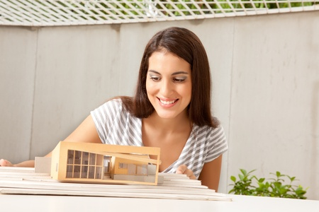 female architect: A female architect looking at a model house