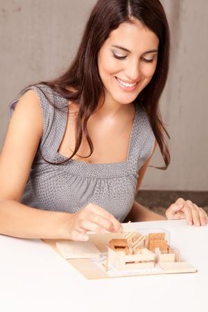 A female interior architect designign a scale model house photo
