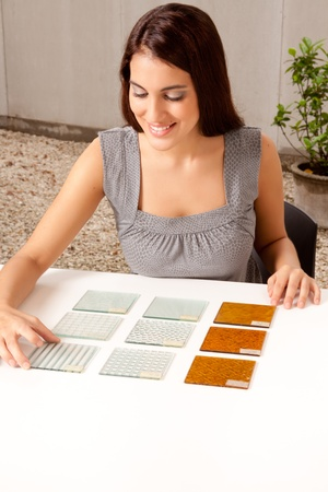 A female architect / designer choosing a glass tile from a group of samples Stock Photo - 9282754