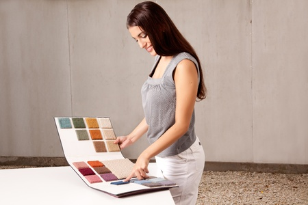 carpet flooring: A female interior architect or designer looking at rug samples from a catalogue