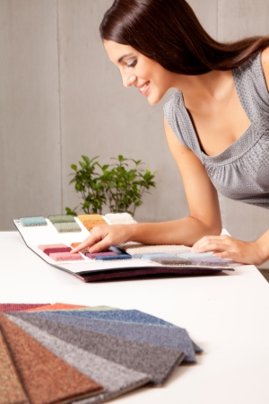 carpet and flooring: A female interior designer looking at rug samples from a catalogue Stock Photo