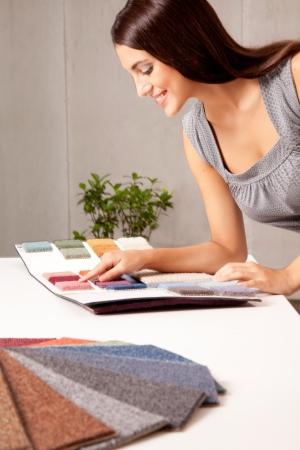designers interior: Un arredatore femmina, guardando i campioni coperta da un catalogo Archivio Fotografico