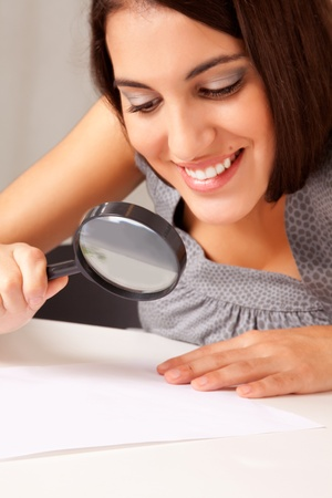 prety: A prety brunette woman looking at a paper with a magnifying glass
