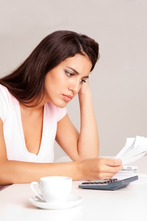 A woman sitting at a desk with calculator and papers planning a budget Stock Photo - 9282622