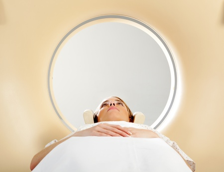 A woman laying down with eyes open having a CT scan photo