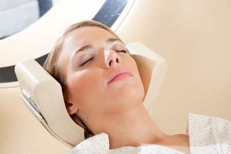 A relaxed woman with eyes closed ready for a CT scan photo