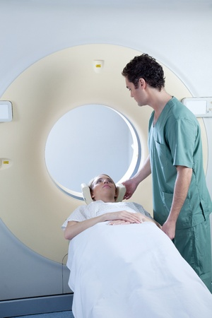 A CT scan machine with patient and nurse photo