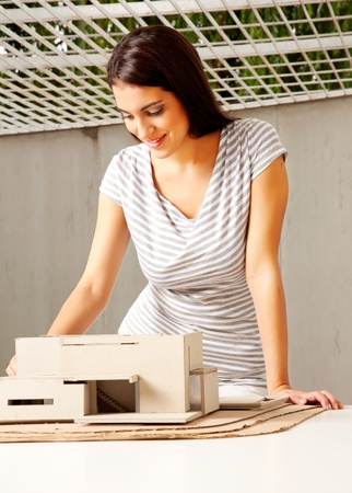 architectural studies: A young female architect looking over a rough model of a house