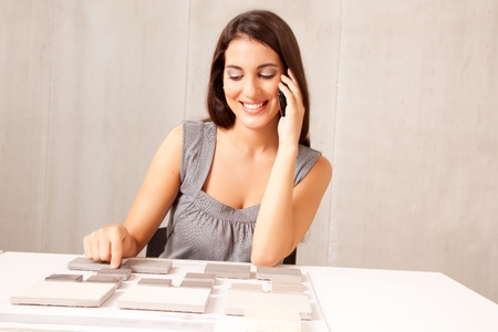 An architect / designer talking on the phone choosing a stone tile Stock Photo - 9330684