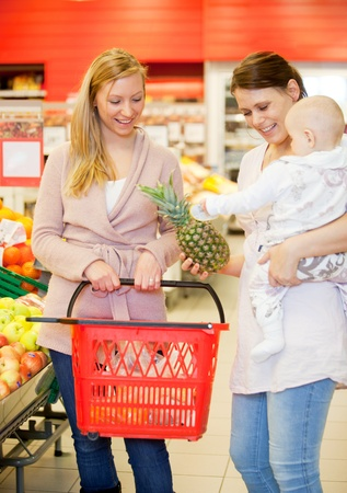 Two friends in grocery store buying groceries with baby photo