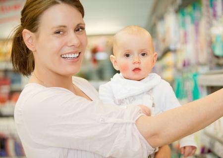 ni�os de compras: Un beb� feliz y madre en una tienda de comestibles comprar comestibles