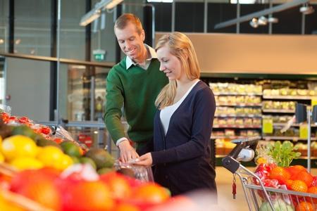 comida rica: Hombre y mujer mirando productos y sonriente en la tienda de compras