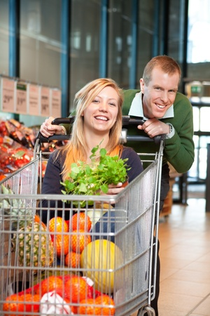Mid adult man in playful mood holding shopping cart while woman sitting in it and looking at camera Stock Photo - 9337064
