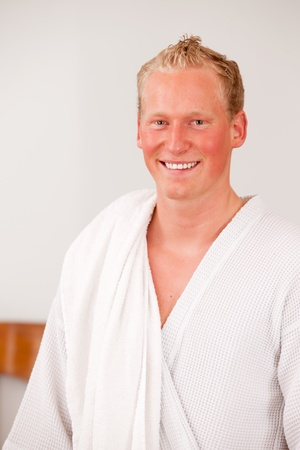A happy handsome bonde man in a bathrobe smiling and looking at the camera photo