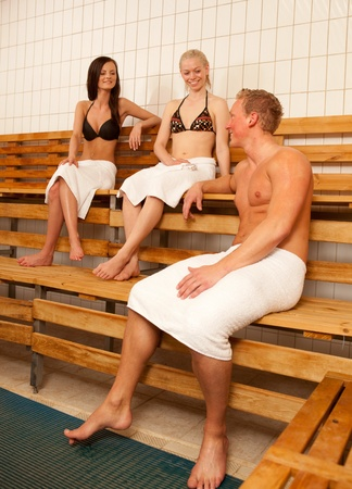 Friends in a Sauna laughing and talking together photo