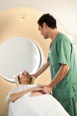 A nurse assisting a patient in a CT scanner giving comfort Stock Photo - 9359442