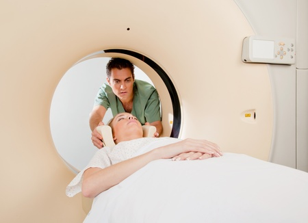 A CT scan technician aligning a patient in the machine photo
