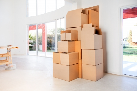 packing boxes: A stack of moving boxes in a new house, ready to unpack Stock Photo