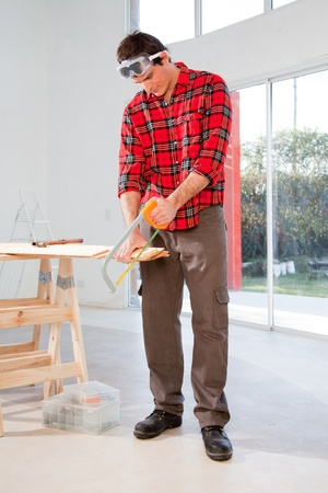 A carpenter cutting wood with a hand saw in a house photo