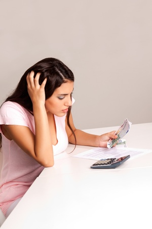 A worried woman counting money and planning a budget photo