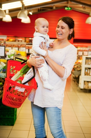 A mother with baby daughter in a grocery store photo