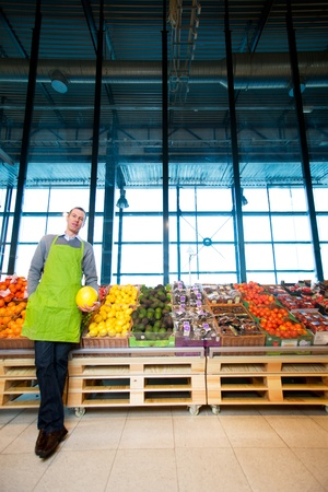 merchant: An owner of a grocery store standing by fruits and vegetables Stock Photo