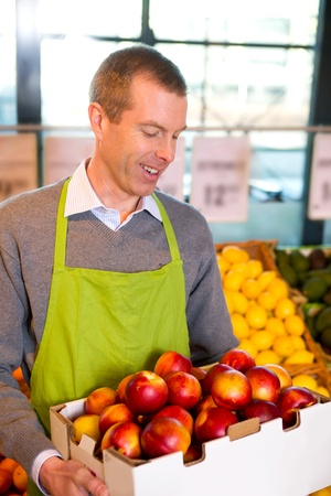 A happy male grocer with a box of ripe peaches Stock Photo - 9359427