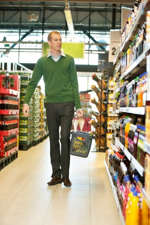 grocery basket: Mid adult man with shopping basket walking in grocery store and looking at products