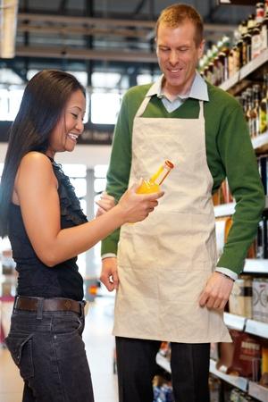 oficinista: Una mujer recibe ayuda de un empleado de la tienda de comestibles - enfoque cr�tico sobre la mujer
