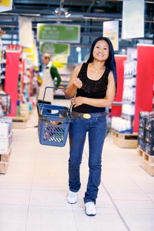 weitermachen: L�chelnd asiatische Frau, die im Supermarkt tragen einen Warenkorb mit Speicher-Arbeiter im Hintergrund