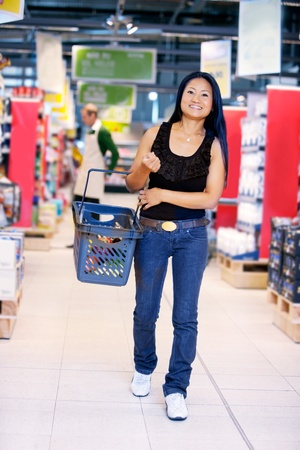 carry: Smiling asian woman walking in grocery store carrying a shopping basket with store worker in the background