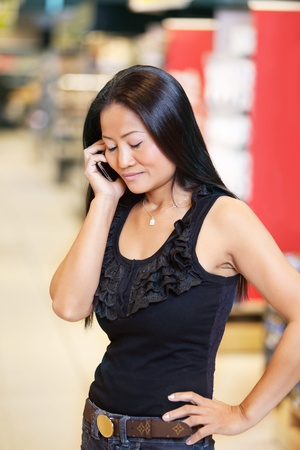 Smiling woman with eyes closed having conversation on mobile phone in shopping centre Stock Photo - 9359410