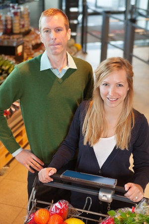 High angle view of smiling woman looking at camera while shopping with man in store photo
