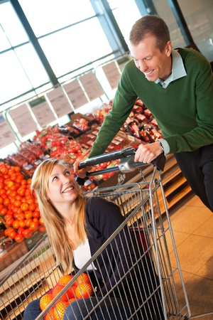 Adult man in playful mood pushing shopping cart while woman sitting in it Stock Photo - 9359438