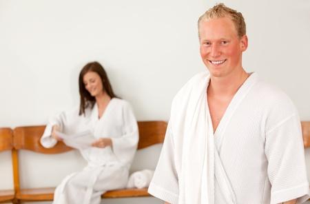 Portrait of a happy man in a bathrobe in a spa reception area photo