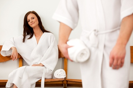 white robe: A coupld in a spa waiting room, shallow depth of field - focus on woman