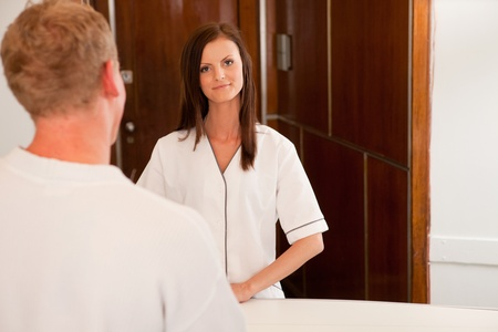 A spa receptionist greeting a male customer at the welcome desk photo