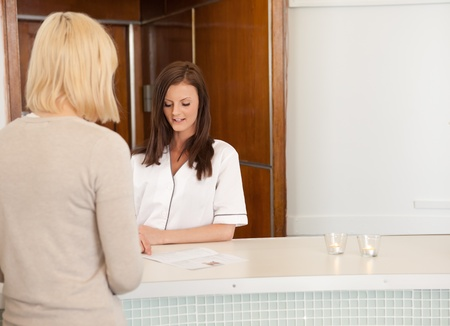A woman in a spa recpetion deciding on a treatment photo