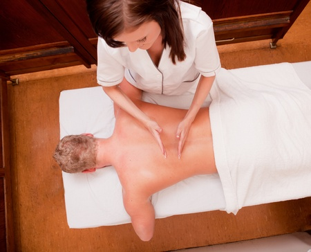 A man receiving a percussive back massage at an old style spa photo