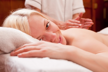 A blond female looking at the camera, receiving a percussive back massage in a spa photo
